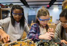 Three girls work on computer circuitry.