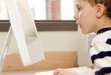 Young boy looking at a computer monitor