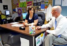 Man sitting at side of desk speaking with woman in the classroom.