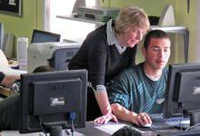 Teacher standing over boy at computer