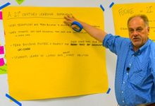 Man pointing to 21st Century Learning Experience notes on big yellow easel paper taped onto a whiteboard