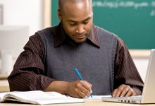 A teacher marks student writing at his desk.