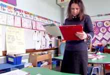 Teacher standing alone in classroom reading off a clipboard
