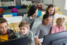 A teacher assists groups of students working at computers.
