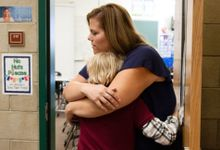 A teacher hugs her student.