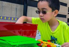Boy wearing glasses building with legos