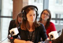 Woman sitting on a panel in front of a microphone wearing headphones with young people sitting behind her