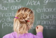 A girl works on a Spanish exercise on a blackboard.