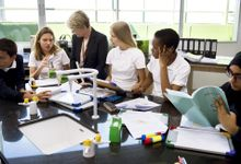A teacher and students gather around a table in their classroom.