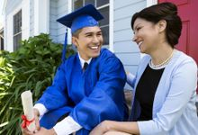 A teen boy in a graduation cap and gown sits on the front porch with his mom—both are smiling.