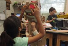 Two students test the fit of a suit of cardboard armor.