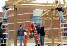 Students and community members framing a building.