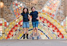 Two girls jumping up in front of a large tiled wall of a sun