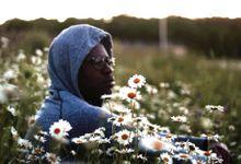 Older boy with grey sweatshirt hood on sitting in a field of daisies