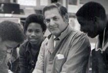 Old picture of man with student in shop class