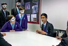 In a classroom, nine students are grouped around a long, rectangular table talking to each other.