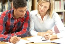A student and teacher discuss the student's college essay.