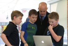 Buddy Berry looks at a computer with students.