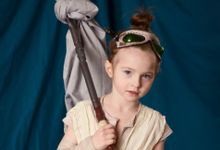A young girl is dressed up in costume as Rey, the female protagonist from the movie Star Wars: The Force Awakens.