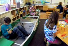 Kids working independently sitting in a canoe, and in groups at a small round table and a square table at floor height