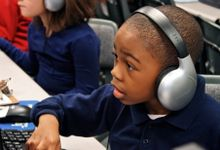 Young boy with some very large headphones working at a computer station