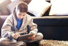 A boy does schoolwork on an iPad on a snow day.