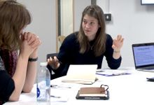 Jess Hughes gesturing with hands, speaking with another teacher