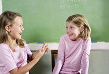 Two second-grade girls role-play a scenario.