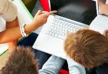 Three people around a laptop