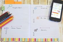 Image of a student's open daily planner with colored pencils and smartphone calendar on the side