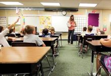 Elementary students are sitting at their desks, looking at the front of the class towards their teacher.