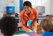 A young female teacher in an orange shirt is standing, bending over holding a book, and smiling while she's looking at two young students sitting at their desks.
