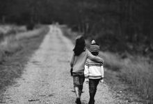 Two young kids are walking away from the camera along a gravel path with tall grass and trees on both sides. They're both wearing jeans and sweatshirts and one of them is wearing a beanie.