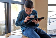 A young boy in a blue sweater and jeans with glasses is sitting on a bench indoors beside a window, holding a tablet and looking at a sheet of paper on the bench.