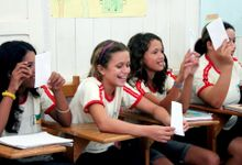 Four preteen girls are sitting in a row at wooden desks, looking in the same direction, smiling, holding up white pieces of paper folded into cards. They're all wearing the same white t-shirt outlined in red around the sleeves and neck.
