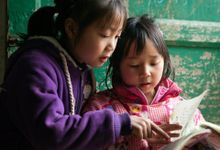 Two young girls, one in a purple sweatshirt and one in a pink sweatshirt, are sitting outside against a green, wooden door, reading together.