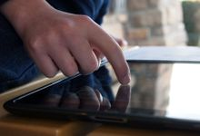 A closeup of a person's hand pressing their index finger against a tablet on a wooden table. In the upper right corner of the photo, there is a blurred corner of brick house and a tall green bush.