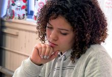 Girl sitting at her desk in deep thought, writing