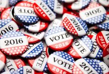 A large pile of red, white, and blue starred pins that say VOTE 2016