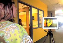 A tripod is standing in the middle of a school hallway with an iPad on it. A student is standing behind it, looking off to the side. Another student is standing between a doorway, looking into the hallway.