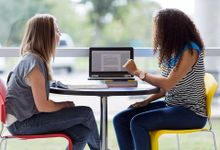 Two teenage girls are sitting at a small circular table with a textbook laid out, looking at a laptop. They're sitting next to a glass wall that looks out to the school parking lot.