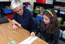 An young girl with rainbow-knitted headphones is sitting at a table with her female teacher. They're both looking at a long, thin sheet of paper, and the young girl is holding the tip of the pencil against the paper, pointing at something.