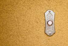 A closeup of a doorbell against a tan, textured wall.
