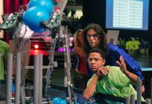 A student and teacher are wearing protective eyewear in an auditorium, looking at a robot.