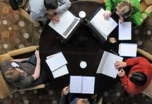 An aerial shot of five teachers sitting around a dark brown circular table in light brown cloth-covered chairs. There are three laptops, four notebooks, and three cups of coffee on the table.