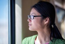 A side shot of a young female teacher in glasses and a green shirt looking out of a window.