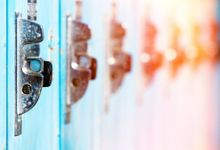 A closeup on 6 adjacent lockers. The first locker is clear and blue, each locker following gets more and more out of focus and shifts into reds and yellows, looking like a rainbow.