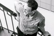 A male teacher in glasses is leaning against a stairway rail, smiling.