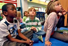 A group of young students are sitting on the floor in their classroom, looking up.