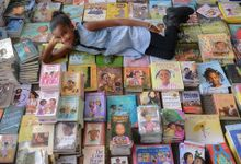 A young black girl is laying down on top of about 300 books stacked together on top of each other, looking up at the camera, smiling.